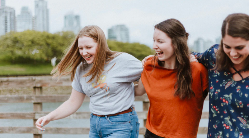 Three young women walking along a bridge with linked arms, laughing