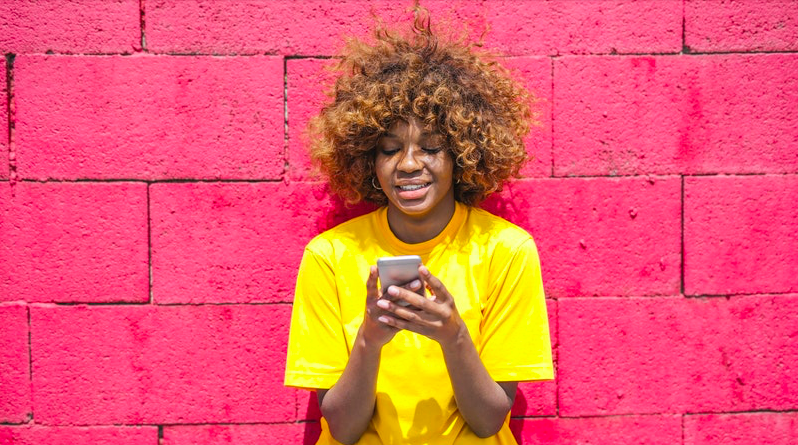 Young woman using phone, smiling