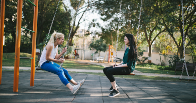 two people in the park on swings facing each other and laughing. The person on the left has long blonde hair in a ponytail and the person on the right has long brown hair