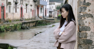 Picture of person looking sad and staring into the distance. There are houses in the background and she is standing by a canal