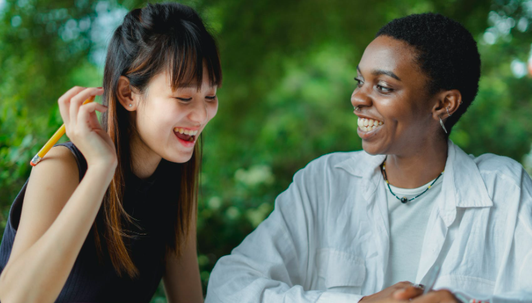 Two young women working together and smiling