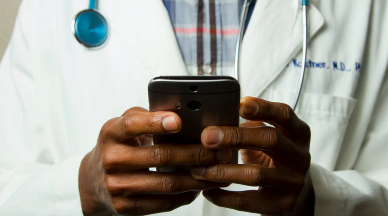 Hands using a phone in front of a person in a white coat with a stethoscope
