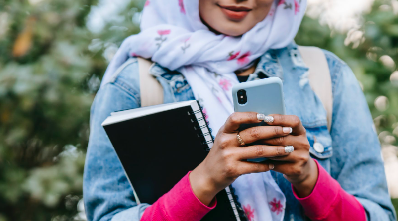 Young woman using phone with leafy background, holding a notebook and wearing a headscarf and denim jacket