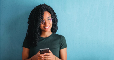 Young woman smiling while using a phone
