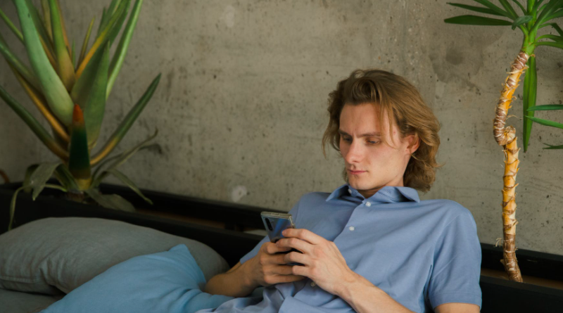 Man using phone reclining on sofa