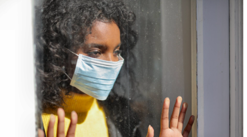 Young woman wearing mask looking out of window longingly with hands pressed against it