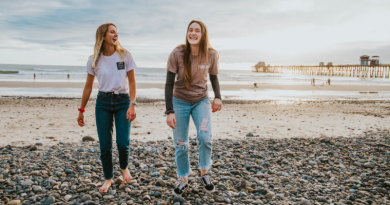 Two young women walking along a pebbled beach laughing