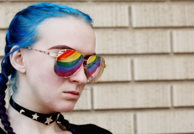 An 18 year old young person with blue hair in plaits wearing sunglasses with the pride flag reflecting in their sunglasses