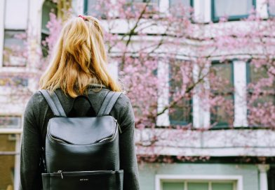 Young woman with backpack facing a building with windows and a tree with pink blossom.